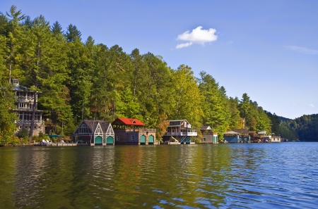 The shoreline of a lake with mountain and houses tapering down under a blue sky.  Lake Rabun in Georgia.