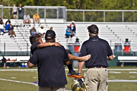 CUMMING, GA, USA - OCTOBER 8 : Unidentified injured player being carried off the field by coaches during a football game; the Raiders vs the Saints, on August 27, 2011 in Cumming GA.