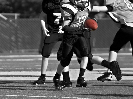 A young boy carrying the ball during a youth league football game, black and white.