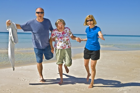 elderly exercise: A family of different generations having fun on the beach.