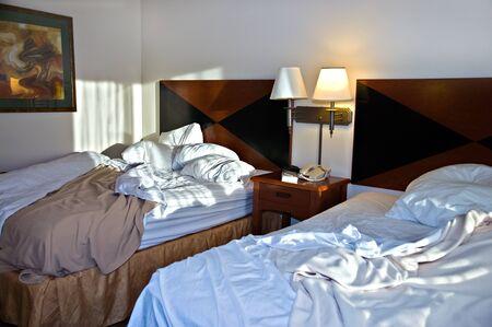 habitacion desordenada: Dos camas en una habitación de un motel después de una noche de sueño.