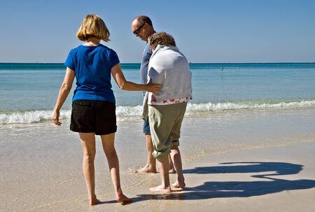 Family caregivers helping an eldery woman enjoy the beach. Zdjęcie Seryjne