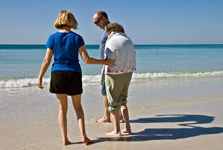Family caregivers helping an eldery woman enjoy the beach. photo