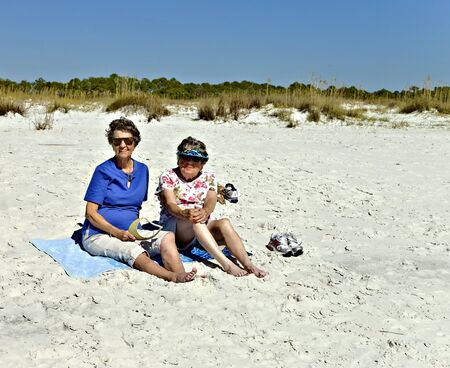 Senior women sitting on towels at the beach. photo