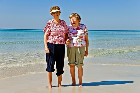 Beautiful senior women together on the beach. photo
