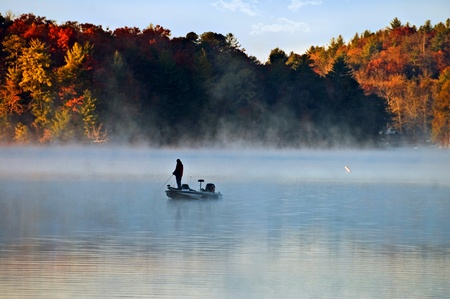early morning: Silhouette of a man fishing in the morning fog with autumn colors on the trees.