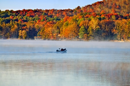 A fishing boat going across the lake in the early autumn morning fog. photo