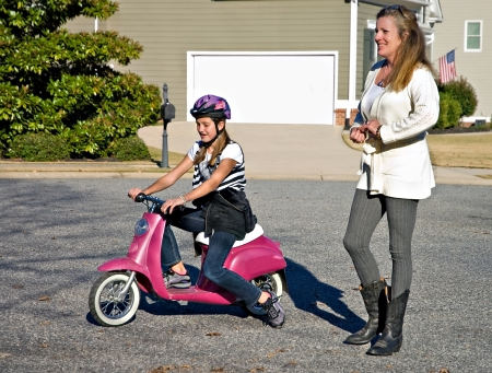 A woman walking with preteen girl while she rides a motorbike.