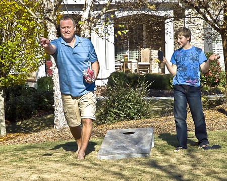 toss: A man and his son playing Cornhole or Bean Bag toss at home.