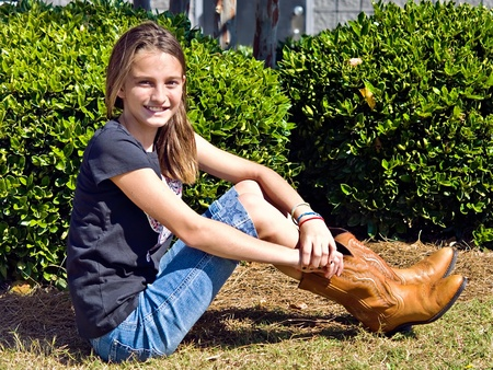 Pretty preteen girl with cowgirl boots sitting outdoors.