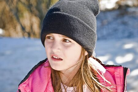 warmly: A young girl dressed warmly out in the snow.