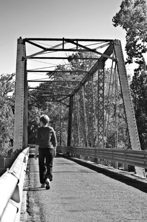 going places: A woman walking across a bridge in black and white. Stock Photo