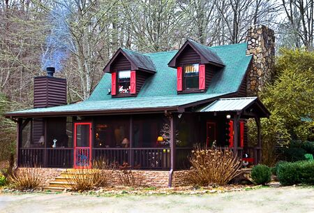 A log farmhouse with Christmas tree on the screened porch and smoke coming from the chimney.
