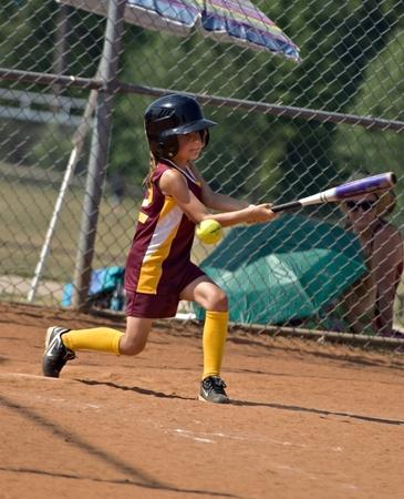 CUMMING, 조지아  미국 - 5 월 21 일 : 미확인 된 어린 소녀 스윙 그러나 조금 리그 소프트볼 경기 도중 카운티, Cumming GA에 공을 2010 년 5 월 21 일이 없습니다