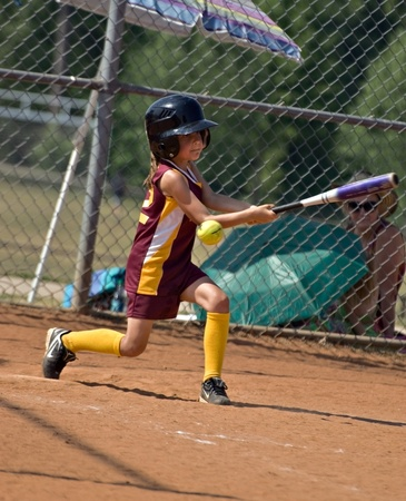 CUMMING, GAUSA - MAY 21:  Unidentified young girl swinging but missing the ball , May 21, 2010 in Forsyth County, Cumming GA, during a little league softball game.
