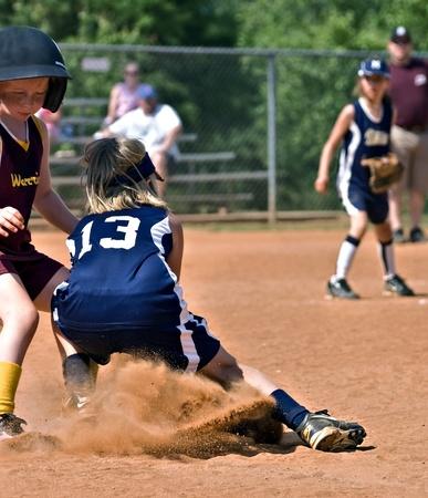 softbol: Cumming, GA  EE.UU. - 21 de mayo: las jóvenes no identificados hacer una jugada en primera base, 21 de mayo de 2010 en el condado de Forsyth, Cumming GA, durante un partido de liga de softbol poco.