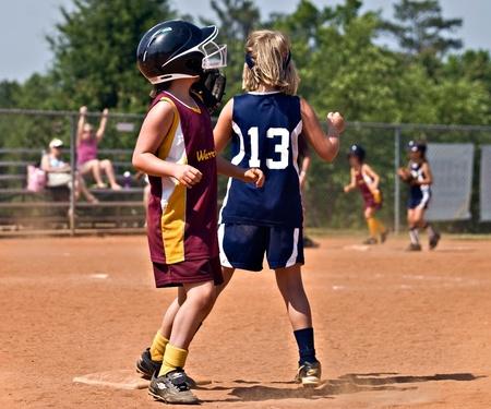 softbol: Cumming, GA  EE.UU. - 21 de mayo: las jóvenes no identificados correr y fildear la bola durante un juego de softball, 21 de mayo de 2010 en el condado de Forsyth, Cumming GA.
