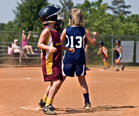 CUMMING, GAUSA - MAY 21:  Unidentified young girls running and fielding the ball during a softball game, May 21, 2010 in Forsyth County, Cumming GA. Publikacyjne