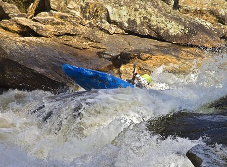 swiftly: Kayaker fighting to stay afloat in the rapids section of a swiftly flowing river