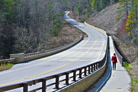 winter road: A woman walking on the path beside a highway