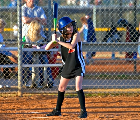 A young girl at bat during a softball game. Zdjęcie Seryjne