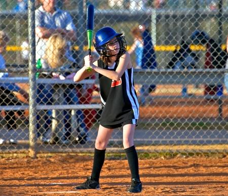 softbol: Un joven al bate durante un partido de softball.