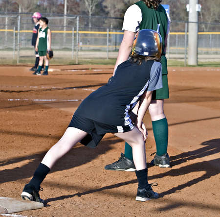 A young girl softball player on base after a hit, ready to run. photo