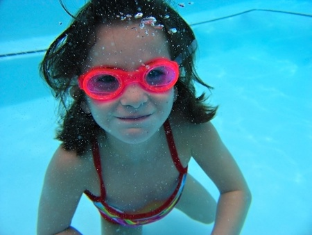 A young girl under water holding her breath and making bubbles.    Banco de Imagens