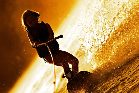 A very young girl on a wakeboard in the early morning dawn, she makes a silhouette against the golden background. Stock Photo