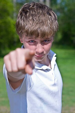 A preteen boy pointing at the camera with an angry expression.