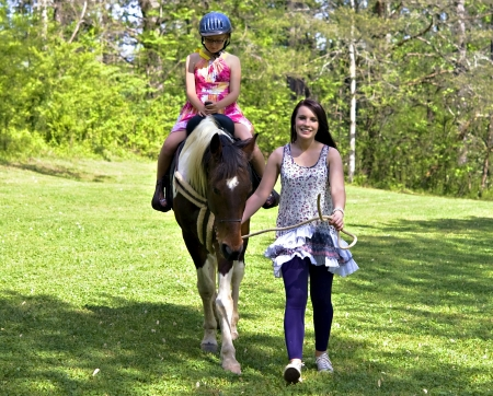 A teenage girl leading a horse with a younger girl learning to ride.