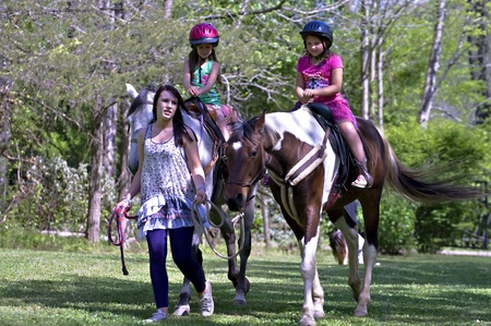 A teenage girl leading a horse with two younger girls learning to ride.