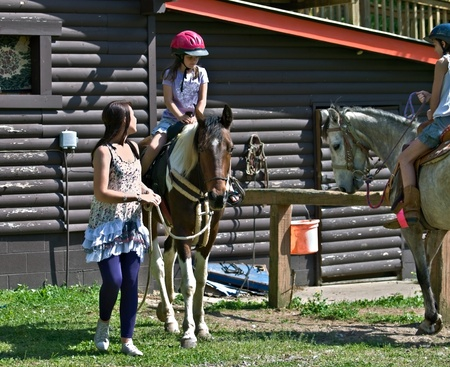 Two young girls at the barn on horses ready ride.  A pretty teenager is leading them out.