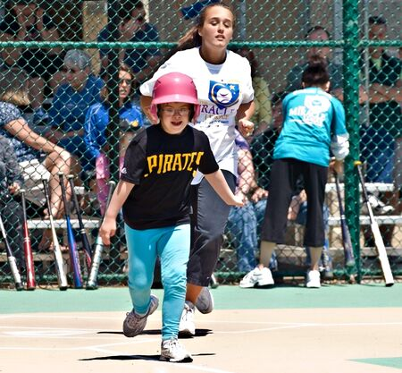 Cumming, GA, USA - Unidentified player and coach on a team in the Miracle League in Cumming, Georgia, April 14, 2012 making a run for first base after a hit. Stock Photo - 13686568