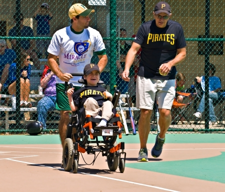 Cumming, GA, USA - Unidentified player and coaches on a team in the Miracle League in Cumming, Georgia, April 14, 2012 making a run for first base after a hit.