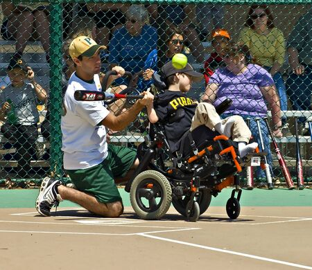 homeplate: Cumming, GA, USA - Unidentified player and coach on a team in the Miracle League in Cumming, Georgia, April 14, 2012 at homeplate making a hit.
