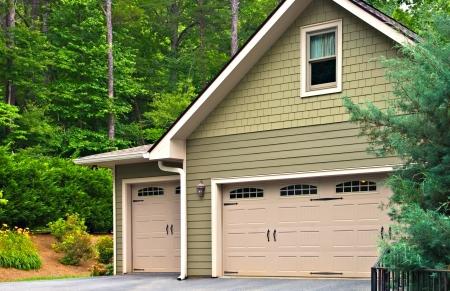 현대 집에 차고 문입니다. 한쪽에는 창문이 있고 옆에 하나씩 오프셋 된 이중 문. 스톡 콘텐츠
