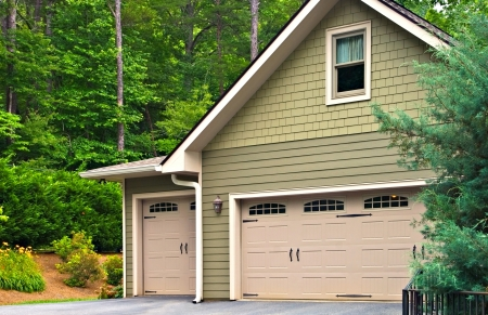 Garage doors on a modern house.  Double doors with windows on one side and an offset single beside it.  Stock Photo