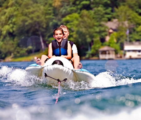 A boy and girl having fun being pulled behind a boat  photo