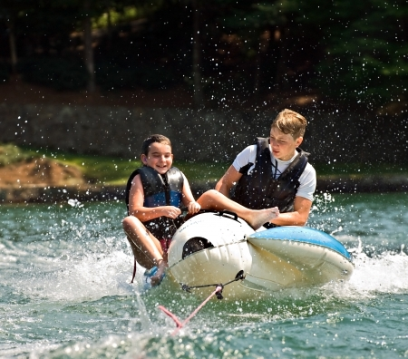 Children on a float behind a boat trying not to fall off  Standard-Bild