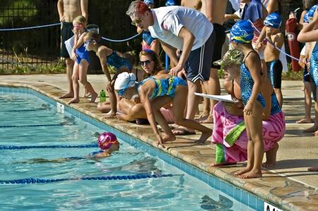 Atlanta, Georgia, 28 Juni, 2012: De jonge zwemmers op een wedstrijd zwemmen voldoen aan het invoeren van het water voor hun schoot. Lake Forest vs St. Marlo.