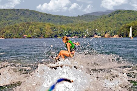 water  skier: A young girl on trick skis falling after hitting a wave  Stock Photo