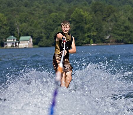 A preteen boy on skis behind a boat  photo