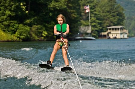 water  skier: A young girl ready to cross a wake on trick skis