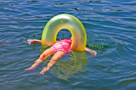 float tube: A young girl looking very relaxed floating on her back in the water  Stock Photo