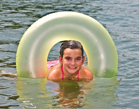 float tube: A cute girl enjoying the water, she has plugs to protect her ears