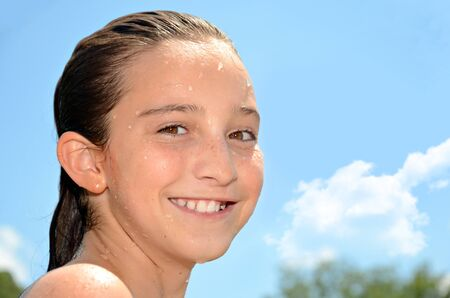 A beautiful preteen girl who is wet after swimming  photo