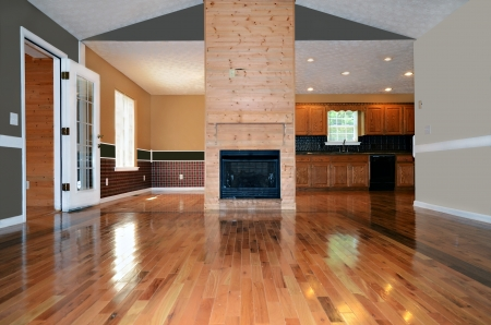 wooden floors: An empty living area with a fireplace.  Behind it is the dining and kitchen area.