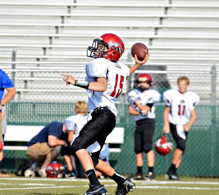 CUMMING, GAUSA - SEPTEMBER 8: Unidentified boy ready to throw a pass during a football game. A team of 7th grade boys September 8, 2012 in Cumming GA. The Wildcats  vs The Mustangs. Publikacyjne