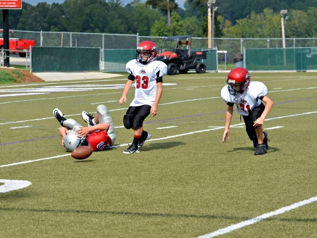 CUMMING, GAUSA - SEPTEMBER 8: Unidentified boy on the ground after missing a pass, as blockers watch. Two teams of 7th grade boys September 8, 2012 in Cumming GA. The Wildcats  vs The Mustangs.